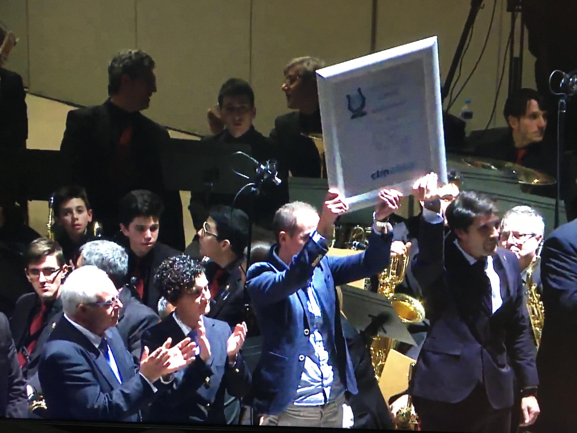 Presidente y director levantan el primer premio conseguido en el 43 Certamen de Altea. Fuente: Certamen Altea.