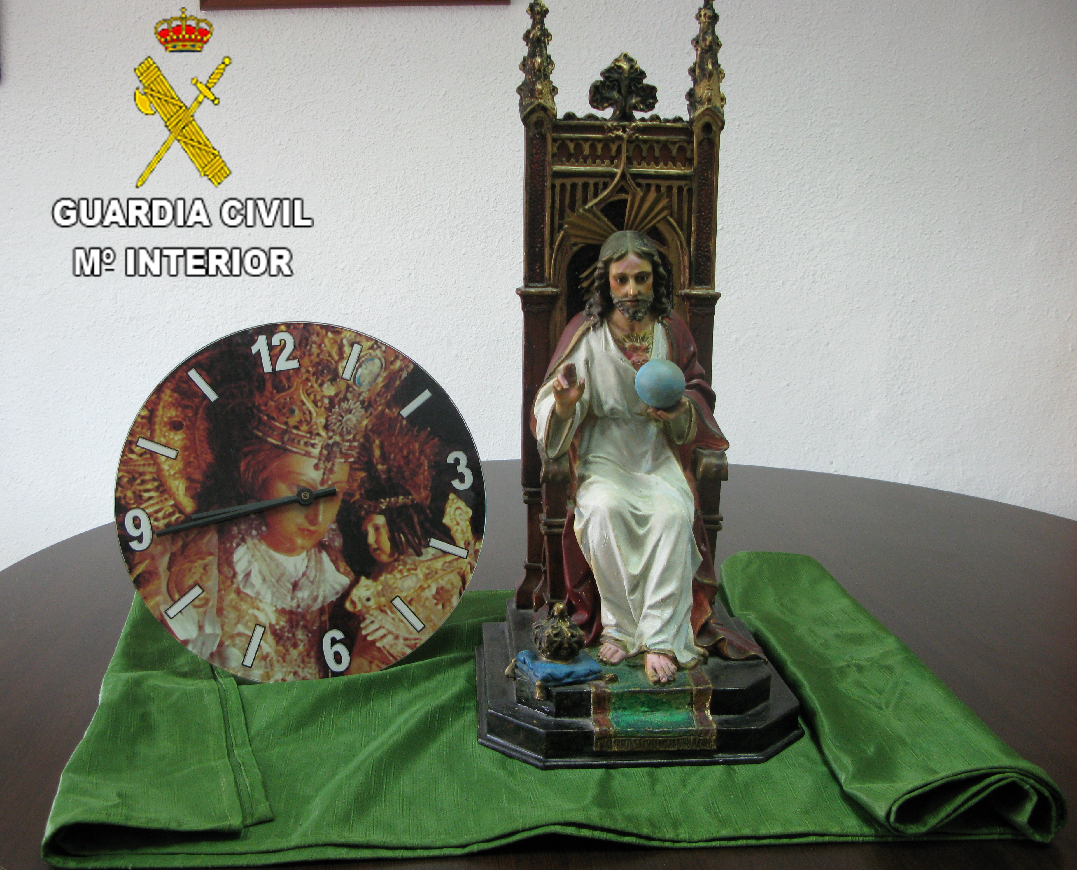 Los agentes en el registro realizado en el domicilio del detenido localizaron los efectos que se trataban de un Cristo Rey en su trono con una altura de 50 cm, un reloj de pared con la imagen de la Virgen y una tela ornamental.