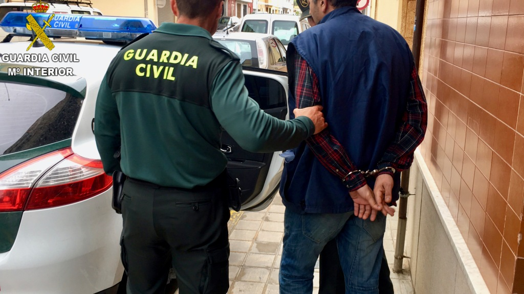 Un agente de la Guardia Civil con el detenido en Chiva.