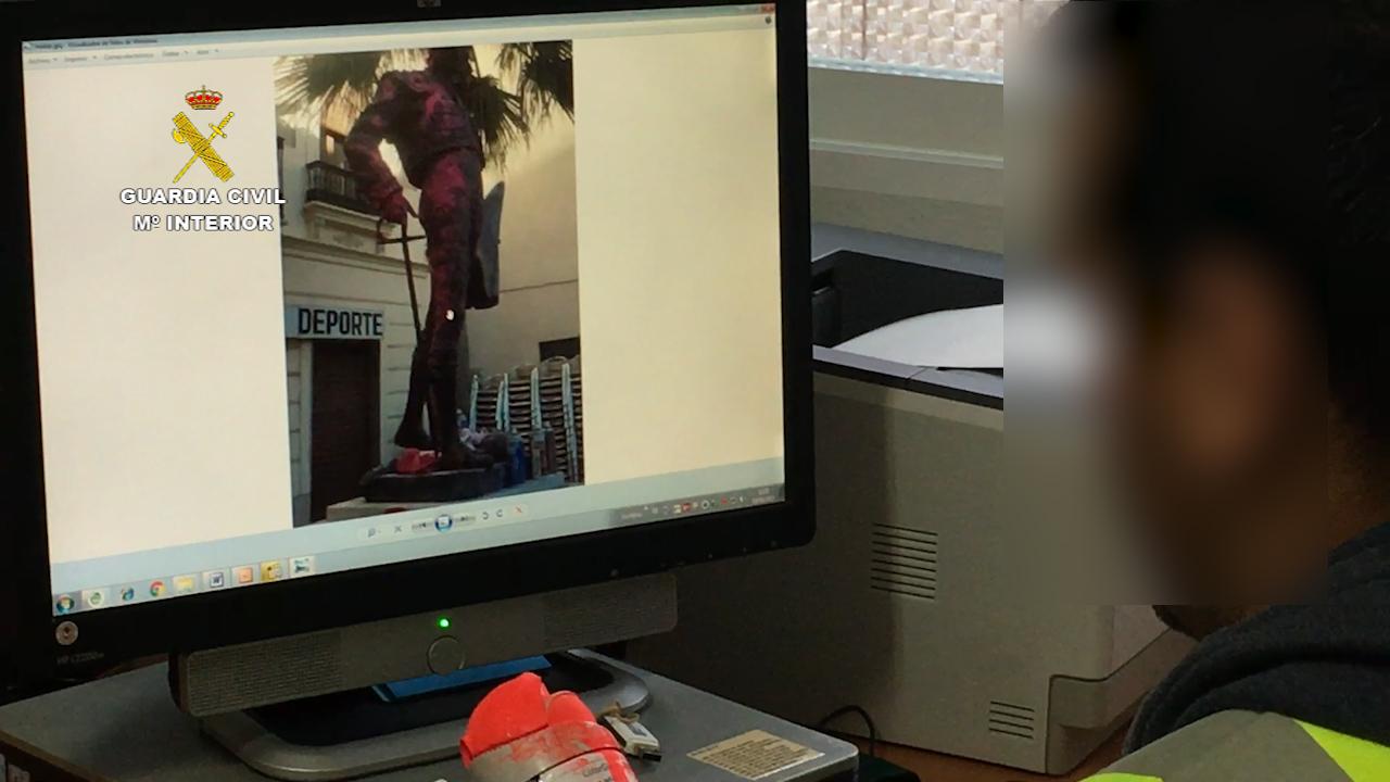 Un agente de la Guardia Civil contempla las pintadas realizadas a la estatua de Ponce en Chiva.