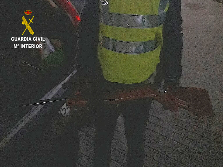 Un agente de la Guardia Civil porta el arma que ha sido incautada al detenido.