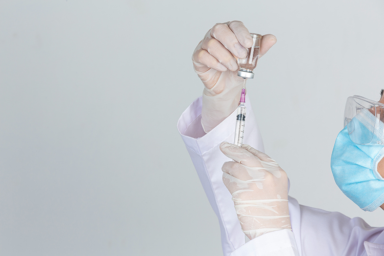 Young doctor is  holding  hypodermic syringe with  vaccine vial